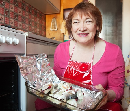 bakeoven: Woman putting scomber with cranberry in griddle into oven