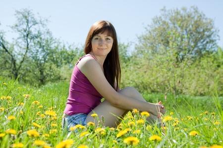 25 to 30: Happy girl sitting outdoor in dandelion meadow