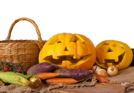Halloween pumpkin and vegetables  on sacking over white background photo