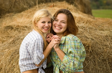 checked shirt: Happy girls on fresh hay at field