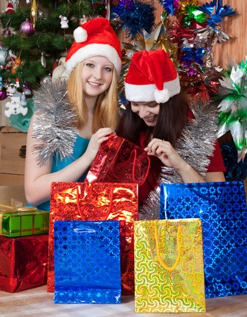 Girls in Santa hats sits with christmas gifts photo