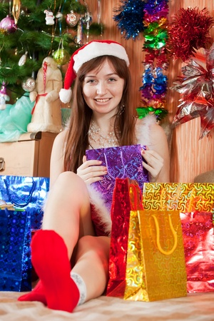 Girl in Santa hat sits with christmas gifts photo