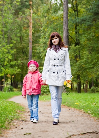 Happy mother with little daughter outdoor in autumn photo
