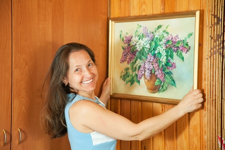 Mature woman hanging art picture on wall at home photo