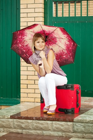 Happy woman with luggage sitting near home door photo