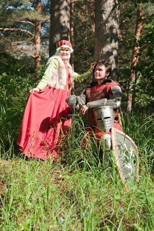 knight in armour and woman in historical costume  at forest photo