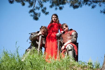cavaliere medievale: donna con due cavalieri in armatura contro il cielo