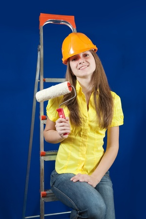 scaling ladder: female house painter with paint rollers on scaling-ladder