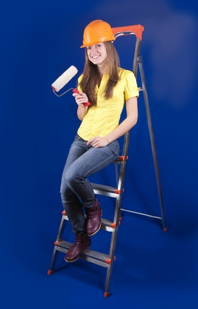 scaling ladder: Girl in hard hat with paint rollers on scaling-ladder Stock Photo