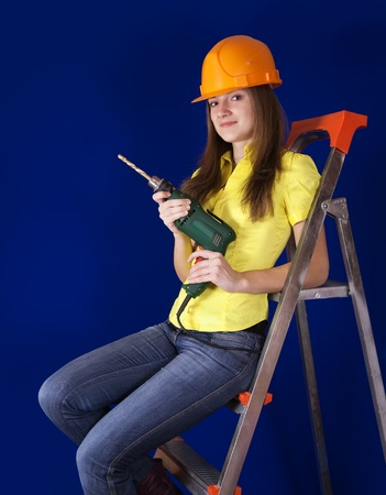 Female construction worker in  hard hat with drill on scaling-ladder photo