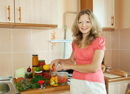 Woman making pickled vegetables in the kitchen photo