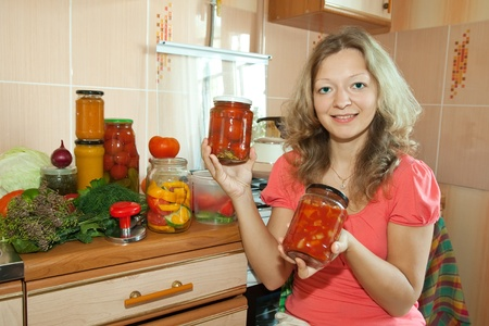 Woman with pickled vegetables in the kitchen photo