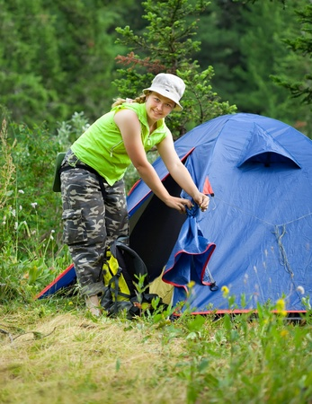 Happy female hiker in front of camp tent outdoor photo