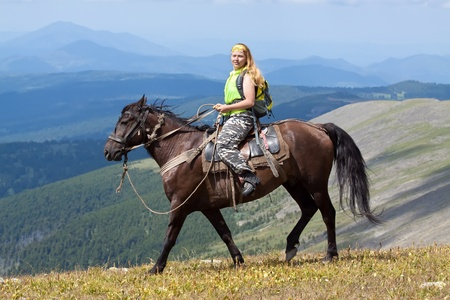 Female tourist with backpack on horseback at mountains photo