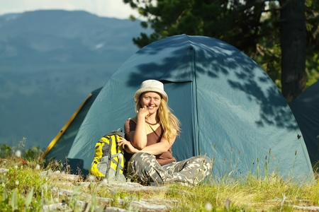 Happy female hiker in front of camp tent against mountains photo