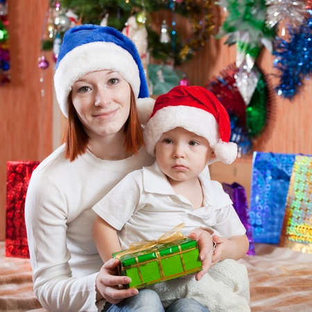 Happy Mother and baby son at home with  Christmas gift  photo