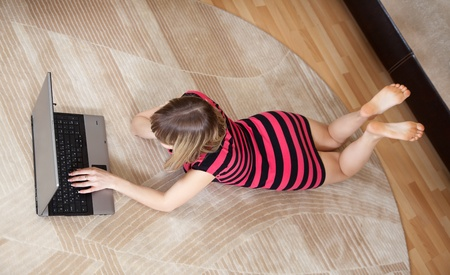 lying down on floor: top view of young girl lying on floor and using laptop Stock Photo