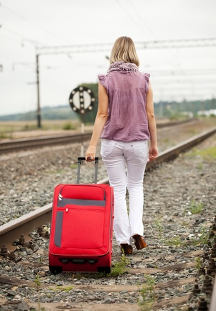 baggage train: Rear view of woman with luggage walking on rail road