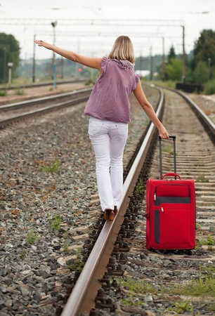 Rear view of woman with luggage walking on rail photo
