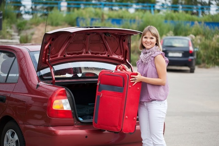 Blonde woman packing her baggage into the car photo