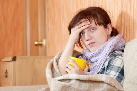 Young illness woman drinking hot tea in blanket Stock Photo - 10352347