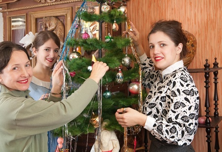 Teen girls with mother decorating Christmas tree at home Stock Photo - 10363334