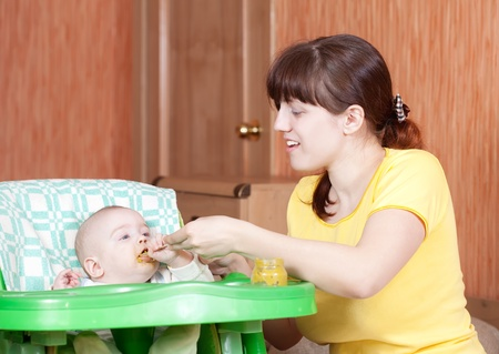 6 month old: Mother feeding her 6 month old daughter with spoon Stock Photo