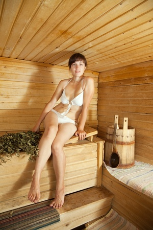 steam room: young brunette woman sitting in sauna