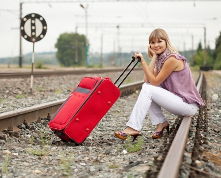 baggage train: woman with luggage sitting on rail