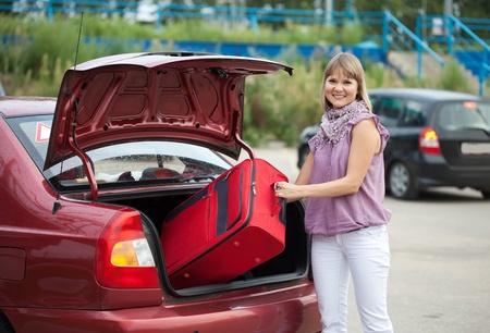 femme avec valise: Femme blonde d�coller valises dans le coffre de la voiture Banque d'images