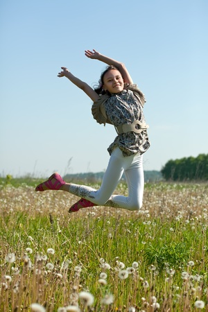 Happy teenager girl jumps at meadow in summer Stockfoto