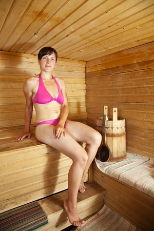 bathhouse: Young woman  sitting on wooden bench  at sauna Stock Photo