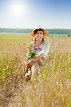 Sitting girl with flowers posy in summer field Stock Photo - 10397802