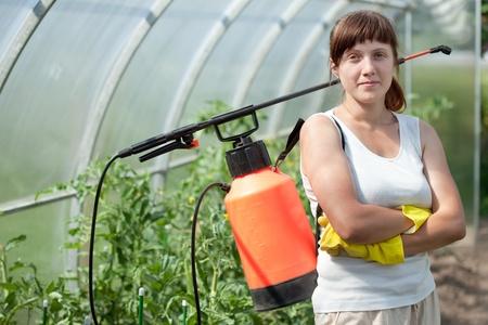 Jardinero femenina con spray jardín de mochila Foto de archivo