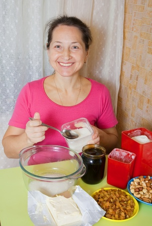adds: Mature woman adds sugar into dish at kitchen table. One of the stages of cooking of  honey cake.  See series Stock Photo