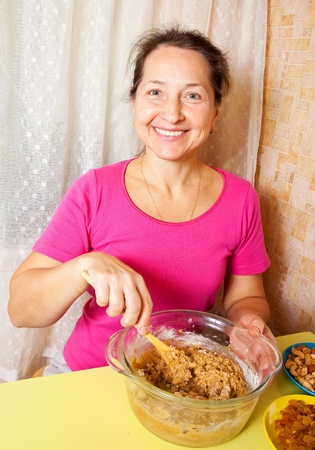 Mature woman making  dough in dish.