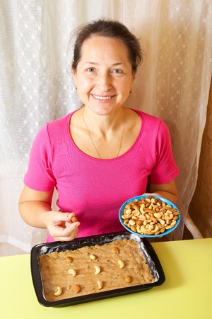 adds: Mature woman adds nuts into dough. One of the stages of cooking of  honey cake.  See series