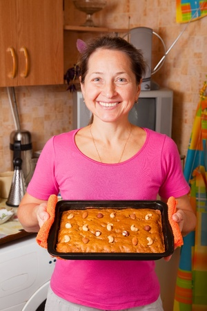 ingridients: Mature woman  with fresh  honey cake. One of the stages of cooking of  honey cake.  See series