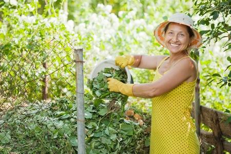composting: Female gardener composting grass in garden Stock Photo