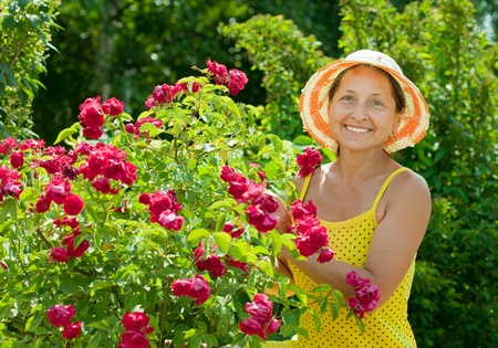 Happy female gardener in roses plant at garden photo
