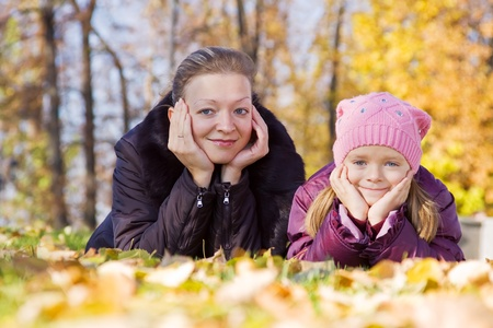 Happy woman with her daughter in autumn park photo