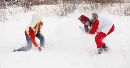 Two  girls plays with snow at winter park photo