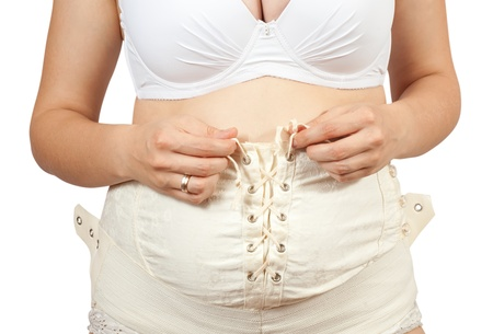 belly bandage:  Closeup of pregnant woman dressing belly bandage. Isolated over white