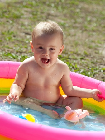 Happy baby swimming  in kid inflatable pool on lawn