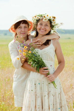 douther: Portrait of two happy women with flowers in summer field