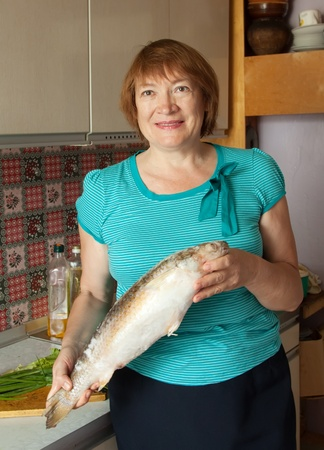 Mature woman with fish in her kitchen photo