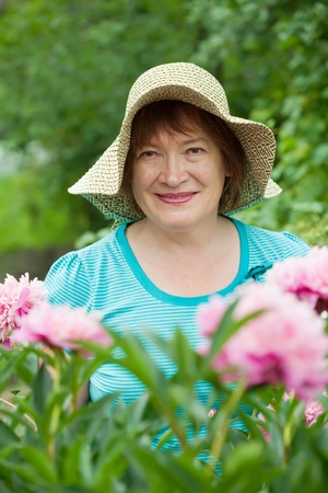 pion: Mature woman in peony plant at garden