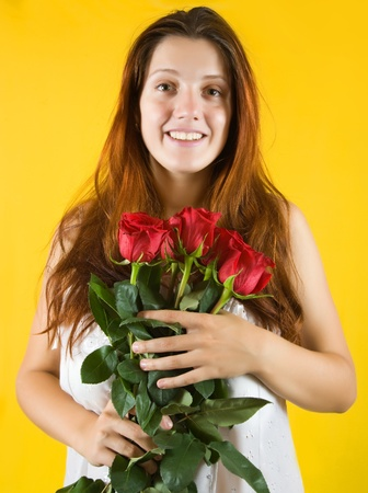 Portrait of  girl with roses on yellow background photo