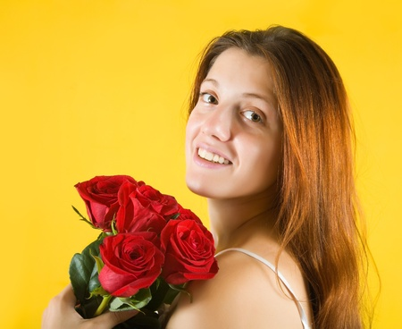beauty  girl with roses isolated on yellow background photo