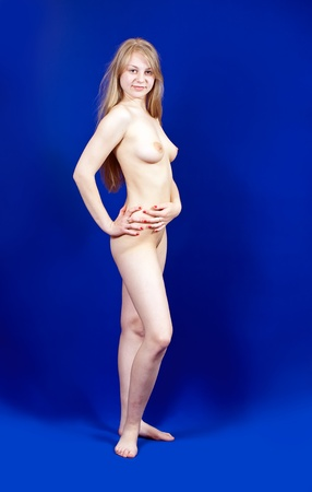 Standing long-haired blonde nudity girl on blue background Stock Photo - 10458861